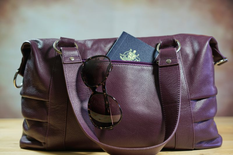 Travel concept with sunglasses and passport in purple carry bag.