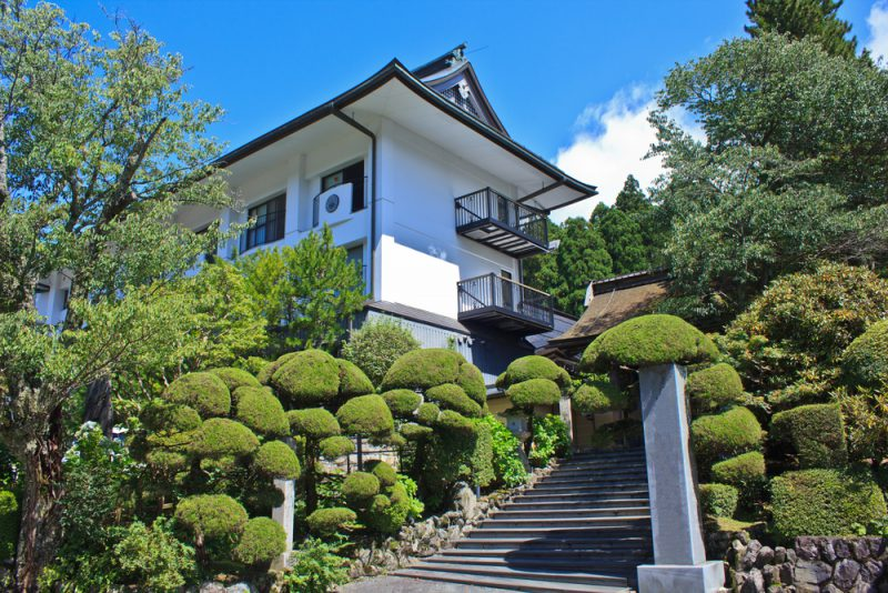 A lush Japanese garden of topiary trees and shrubs lines the entrance to a Buddhist temple in Koyasan