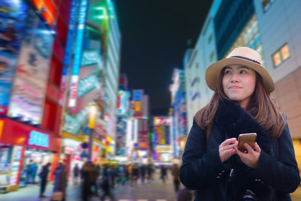 Asian woman tourist is using smart phone connecting at Akihabara back ground in Tokyo, Japan