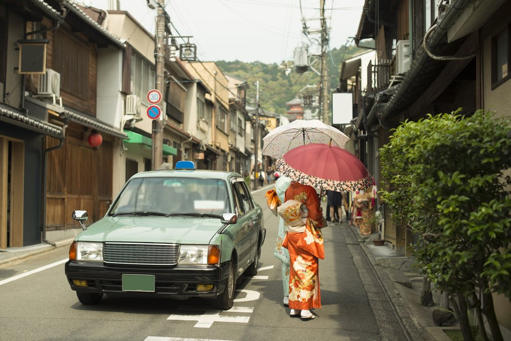 Vintage street scene in Kyoto province, Japan with taxi car and females wearing Yukata and handling traditional umbrellas
