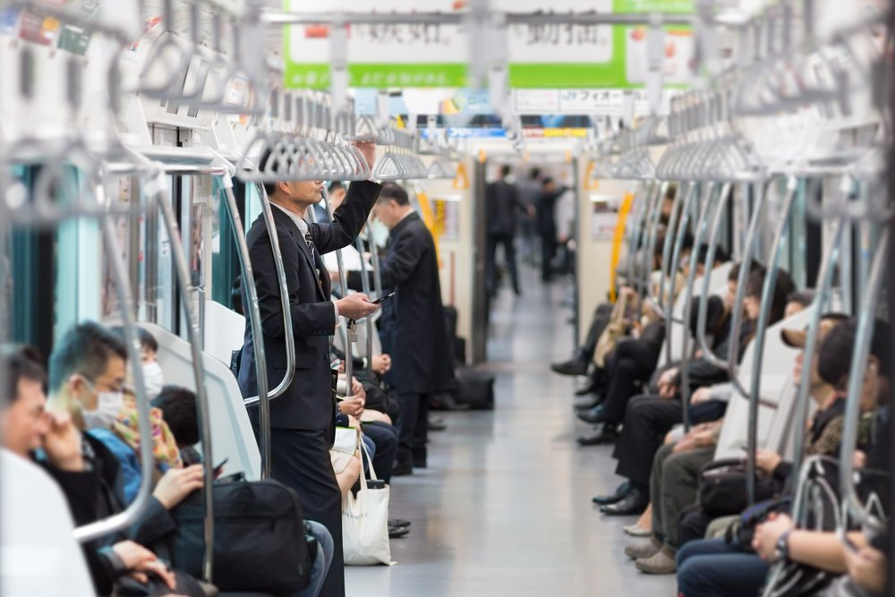 Passengers traveling by Tokyo metro. Business people commuting to work by public transport in rush hour