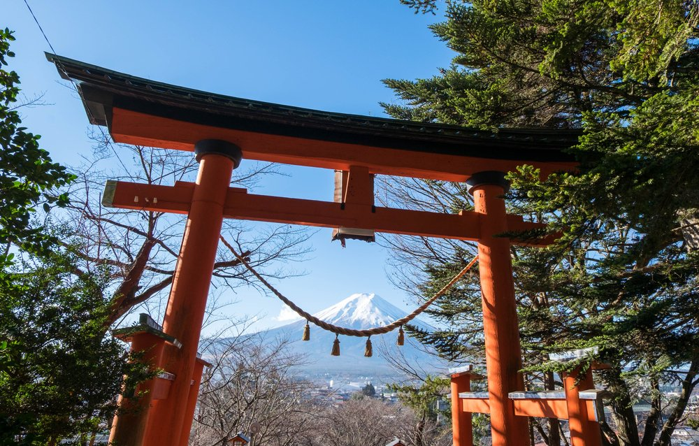 Red torii of Chureito temple with Mount Fuji as background. The gate and rope look like smile
