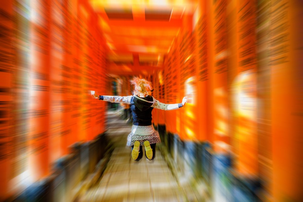 Buddhist temple defocused background. Adventure, exploration, travel concept. Happy tourist woman jumping under red torii gates with blurred motion effect. Fushimi Inari shrine, Kyoto, Japan.