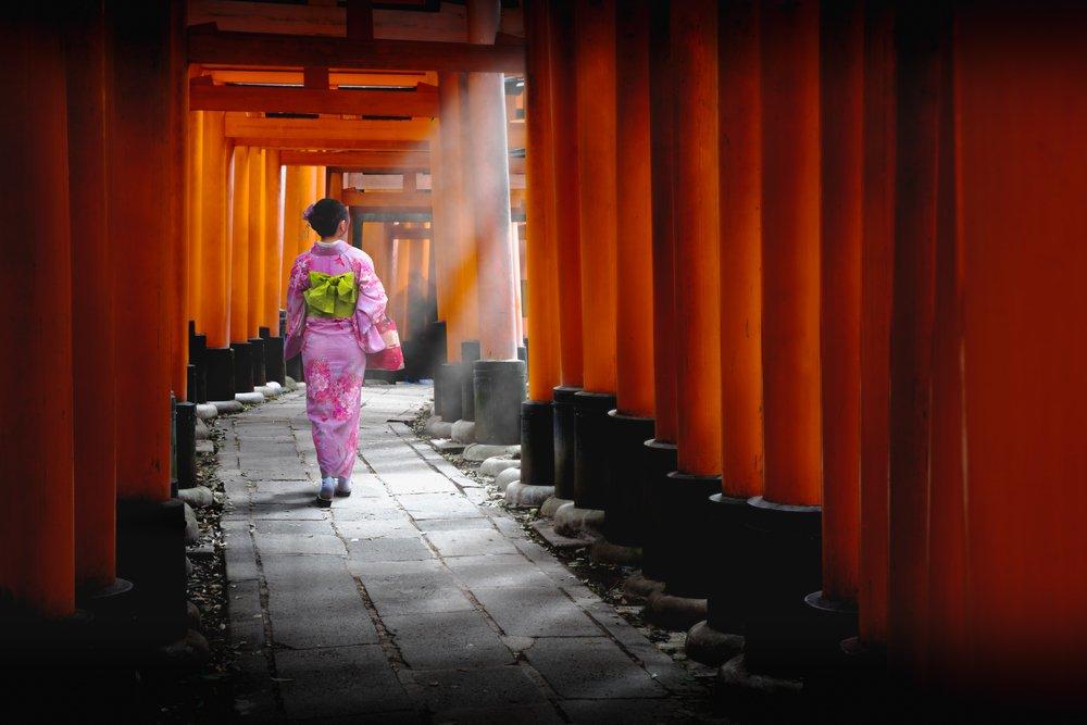 Woman dressed in traditional japanese costume walking under tori gates at the fushimi-inari shrine, Kyoto