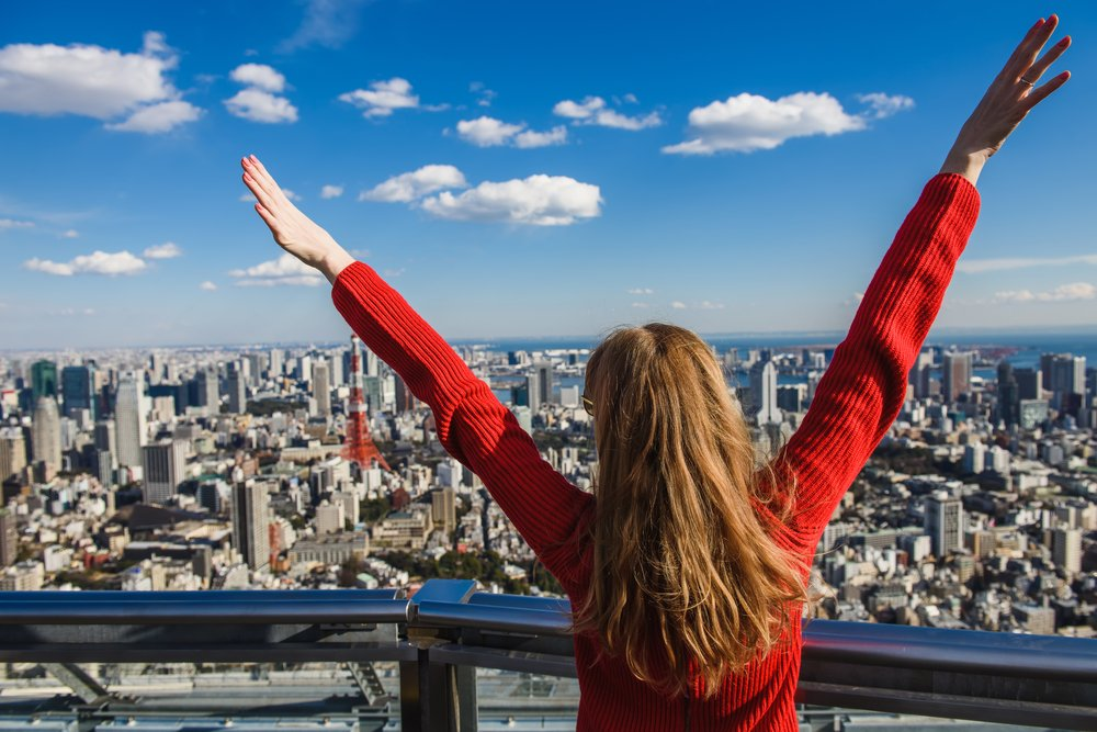 oung woman with her hands up. Girl stands with her back. Tokyo Tower with skyline